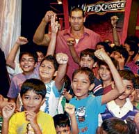 Dilip Singh Rana alias 'The Great Khali' poses with children during the launch of toys at a shop in Mumbai on Saturday. PTI