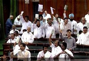 TV GRAB: Members disrupt the proceeding in the Lok Sabha in New Delhi on Wednesday. PTI