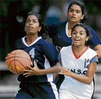 Aaiming high:  Rajmahal's N Anaga (left) moves past VNS' Trisha in the State Youth basketball championship. DH photo
