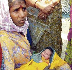 A woman holding a new born baby left in a cradle