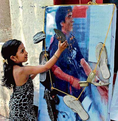 reap what you sow: A child slaps a poster of Pakistani terrorist Ajmal Kasab with a slipper while celebrating the death sentence awarded to him in Mumbai on Sunday. PTI