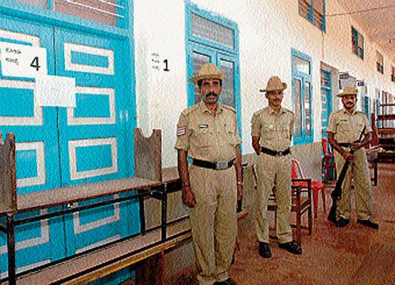 Policemen guarding the strong  room where  ballot boxes are kept at Rosario PU college in Mangalore on Thursday. DH photo