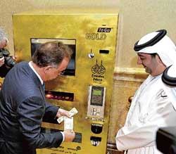 "gold diggers: Thomas Geissler, the chief executive of TG-Gold-Super-Markt, tries the ""Gold to Go"" vending machine at the Emirates Palace Hotel in Abu Dhabi on Wednesday. AFP"