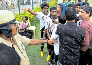 Tempers flare:  A police officer and organisers try to pacify Vasco players at the Bangalore Football Stadium. DH photo