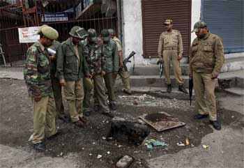 Police inspect the site of a grenade explosion in Srinagar on Friday. AP
