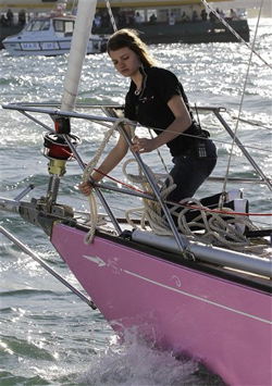Sixteen-year-old Jessica Watson works with the rigging as she sails past the finish line at the entrance to Sydney Harbour in Sydney, Australia on Saturday. AP