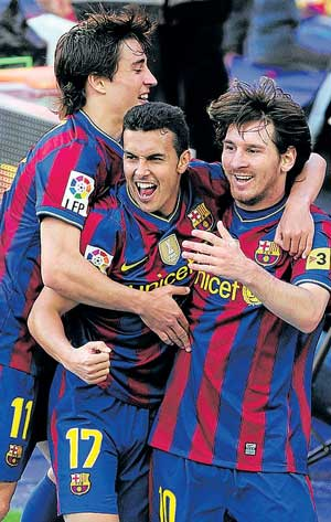 Barcelona's Lionel Messi (right), Pedro  (centre) and Bojan Krkic celebrate after their team  retained the La Liga title on Sunday. Reuters