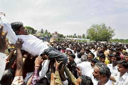 the winner takes it all: Supporters lift a winning candidate outside a counting centre at Kengeri in Bangalore on Monday. dh Photo