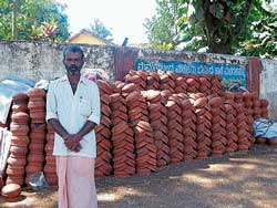 still in demand K T Murugan with earthen utensils in front of the Forest Department in Narasimharajapur. DH photo