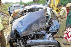 Police inspecting the mangled car involved in an accident near Anesidri village, Hiriyur taluk on Thursday. dh photo