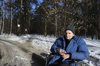 Brave crusader: Mikhail Beketov sits in a wheelchair outside a hospital on the outskirts of Moscow. NYT