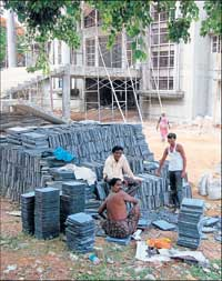 The workers preparing to lay the floor tiles at the indoor stadium in Kolar. DH Photo