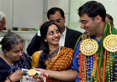 World Chess Champion Viswanathan Anand showing his medal to his mother as his wife Aruna looks on, on his arrival at the Chennai airport on Monday. PTI