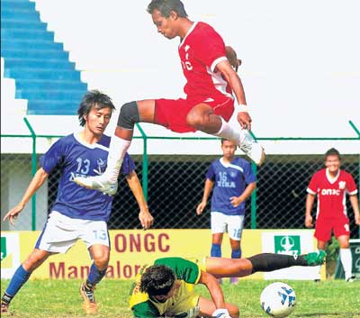 TIMELY TACKLE: NISA goalkeeper L Prem Kumar Singh (on the ground) thwarts Tarif Ahmed of ONGC in the I-League Second Division match on Tuesday. DH PHOTO