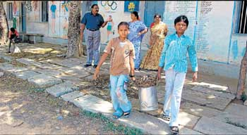 Students of government school in PC Colony in Kolar engaged in cleaning work on Friday. DH PHOTO