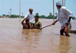 in deep trouble: Men carry an elderly villager to safety through flood waters near Patiala in Punjab on Thursday. AFP