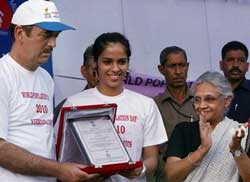 Union Health Minister Ghulam Nabi Azad (L) Delhi's Chief Minister Shiela Dikshit felicitate badminton player Saina Nehwal during a function organized on the occasion on 'World Population Day' at Rajpath in New Delhi on Sunday. PTI