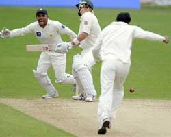 Australia's Shane Watson, center, reacts as Pakistan's Umar Amin, right, takes his wicket during the second day of the second test at the Headingley cricket ground, Leeds, England. AP