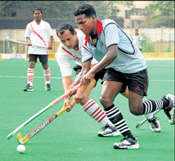 Praful K (right) of MLI tries to tackle Tanu Nanjappa of RBI in the Travancore Cup hockey meet. DH photo