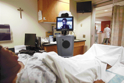 ARTIFICIAL INTELLIGENCE: Dr John Whapham, a neurologist pictured in the monitor of a mobile robot, sometimes called a telepresence robot, speaks with a patient at Loyola University Medical Centre in Maywood, Illinois. NYT