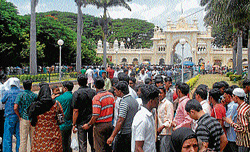 Tourists making a beeline to buy entry ticket to Palace, in Mysore on Sunday. A long queue was witnessed throughout the day outside the ticekt counter, even as thousands thronged the palace. dh photo