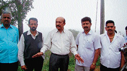 MLC M C Nanaiah speaking to presspersons after inspecting the encroached government land in Madikeri. DH PHOTO