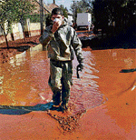 A Hungarian firefighter walks through a street flooded by toxic red sludge. AP