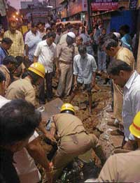 Tragedy:  A team of firemen and Corporation staff search for the body of Kumaraswamy  Hiremath, who was washed away in rainwater in an open drainage at Radhakrishna Galli in Hubli on Friday. KPN