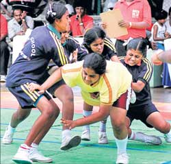 PVP High School girls grab Manasa of Bhoruka English School in the kabbadi competition during the Bangalore School Games on Saturday. DH photo