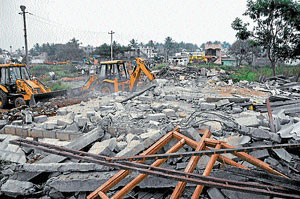 Earth moving machines razing the illegal constructions near Devanur lake in Mysore on  Tuesday. dh photo