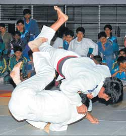 Rohini B Patil of Belgaum (top) pins down team-mate Kavitha M to  pocket the women's above 78kg gold in the State judo championships on Tuesday.  DH Photo