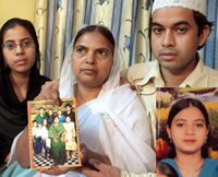 A file photo of  Shamima Kausar, mother of Ishrat Jahan (inset), holds a group photo of the family while standing with her daughter and son