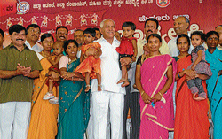 Chief Minister B S Yeddyurappa seen with the beneficiaries of 'Bhagyalakshmi' scheme at the launch of the programme in Mysore on Saturday. Medical Education and District In-charge Minister S A Ramdas, Woman and Child Development Minister C C Patil, Forest Minister C H Vijayashankar are seen. DH Photo