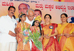 Chief Minister B S Yeddyurappa with Dakshina Kannada district's  first two Bhagyalakshmis Likitha and Akshitha  at the distribution of sarees to the beneficiaries of Bhagyalakshmi scheme in Puttur on Wednesday. DH photo