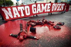 red ire: Demonstrators covered in red paint block a main avenue leading to the Nato convention centre in Lisbon on Saturday. AP