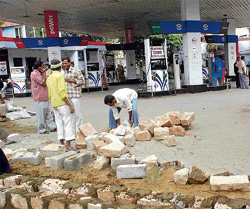 in action: BBMP workers build a wall to shut down the operations of a petrol bunk at  Jayanagar, in Bangalore on Tuesday, as its lease period expired. KPN