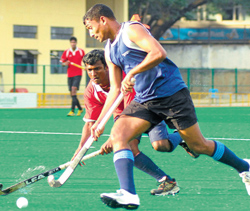 vying for the ball: Krishna Patil (foreground) of MLI tries to go past Ramakrishna of CoE during  their Super Division hockey match at the KSHA on Friday. dh photo