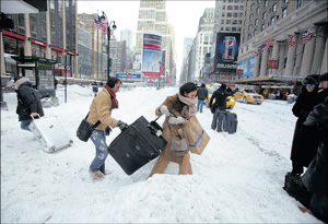 Travellers carry their luggage through a snow bank on 7th Avenue in front of Penn Station after a  snowstorm in New York on Monday. Reuters