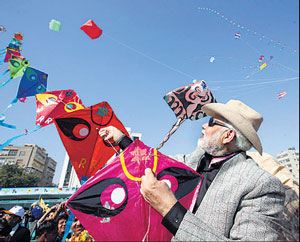 Chief Minister Narendra Modi manages his string of kites  at the international kite festival in Ahmedabad on Tuesday. Photo by K Bharwad
