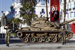 On high alert: A Tunisian army soldier gestures as he stands guard near a tank in downtown Tunis on Friday. Reuters