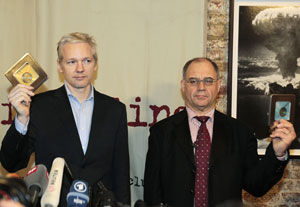 WikiLeaks founder Julian Assange and former Swiss banker Rudolf Elmer display two CDs containing details of money stashed in Swiss banks, in London on Monday. AP