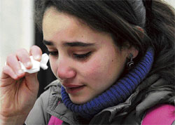 No respite: A schoolgirl wipes her tears outside her school in Tunis on Monday. Teachers across Tunisia have gone on strike demanding members of the former party of the ousted president stay out of power, on the day when schools were set to reopen after weeks of closure amid unrest and street protests. AP
