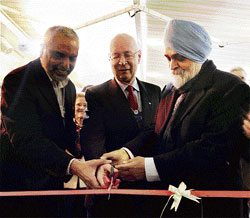 Planning Commission Deputy Chairman Montek Singh Ahluwalia (right) with Confederation of Indian Industry President Hari S Bhartia and World Economic Forum (WEF) Founder & Executive Chairman Klaus Schwab (centre) inaugurating the India Adda Cafe at WEF, in Davos, on Wednesday. PTI
