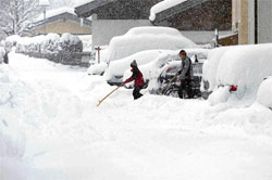Severe winter: People clearing snow from a street in Lofer in the Austrian province of Salzburg in December 2010. (AP Photo/ Kerstin Joensson)