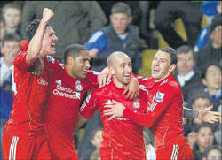 Liverpool players swamp Raul Meireles (second from right) after he scored the winner against Chelsea during their EPL clash at Stamford Bridge on Sunday. AP