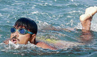 Prakash Kharvi swimming with his hands cuffed behind. DH Photo