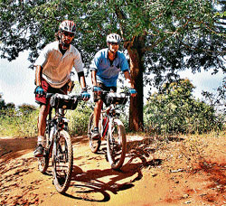 Passion: Krishna Vasudeva Rao and Krishna Chaudhari on a cycling expedition to H D Kote.  (Right below)The duo set-up a tent enroute to Kodaikanal. (PICs by special arrangement)