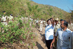 Look out: Excise Minister M P Renukacharya directing personnel of  the Excise Department to take action against bootleggers during a raid on the hillocks near Kharvi village in Belgaum taluk on Thursday. DH photo