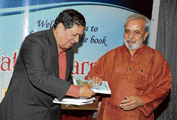 Lokayukta Justice N Santosh Hegde hands over 'Natak Karnatak' book to writer U R Ananthamurthy, after its release at a programme organised by Prarthana Books in Bangalore on Thursday. DH Photo