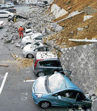 Vehicles are crushed by a collapsed wall at a carpark in Mito city in Ibaraki prefecture after a massive earthquake and tsunami rocked Japan on Friday. AFP